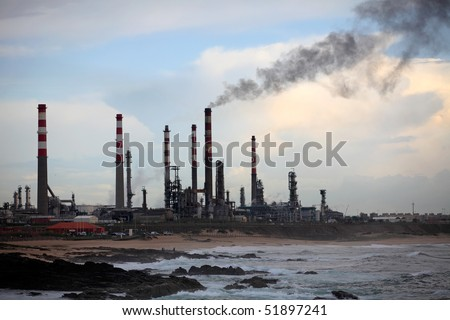 Part of an oil refinery near the sea seeing dark smoke - late evening light - stock photo