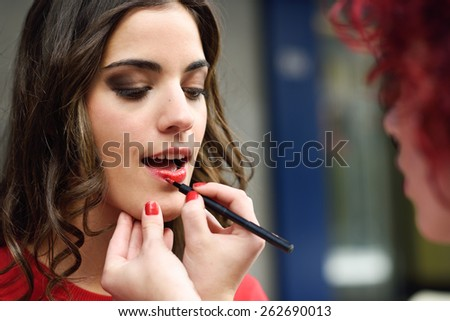 Part of attractive woman's face with fashion red lips makeup. Make-up artist apply bloody lipstick - stock photo