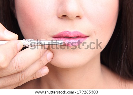 Part of attractive woman's face with fashion red lips makeup. Make-up artist apply lipstick - stock photo