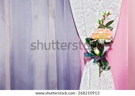 Part of beautifully draped curtain with patterns and a flower - stock photo