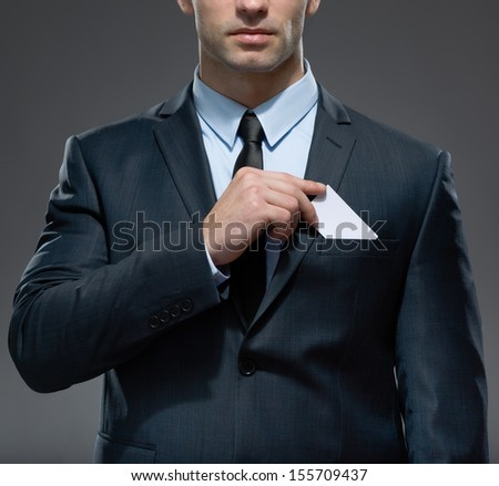 Part of body of man who takes out white card from the pocket of business suit, copyspace - stock photo