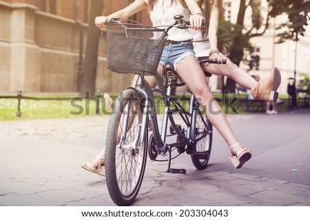 Part of boho girls legs during riding tandem bike - stock photo