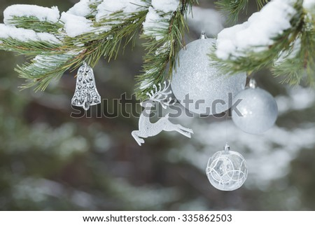 Part of decorated Christmas tree with animal Santa Claus's reindeer ornament and silver baubles on snowy spruce branches - stock photo