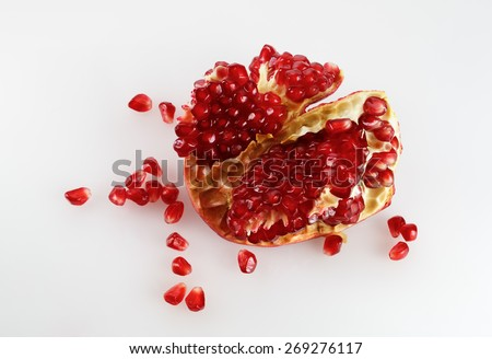 Part of delicious juicy ripe pomegranate and pomegranate seeds scattered around. Studio shot. Top view.  - stock photo