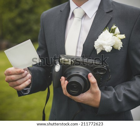 Part of groom with retro camera and empty card - stock photo
