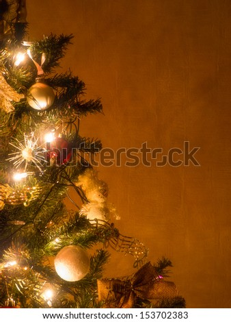 Part of lit christmas tree on brown wall - stock photo