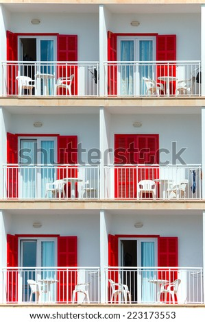Part of luxury hotel with red shutters. - stock photo