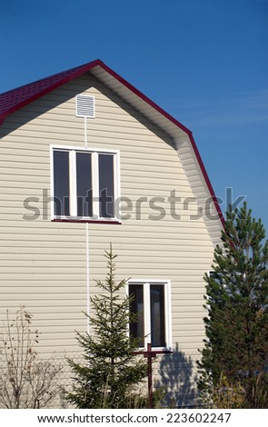 Part of new built country house with red roof of metal tile and covered with beige siding on sunny day - stock photo