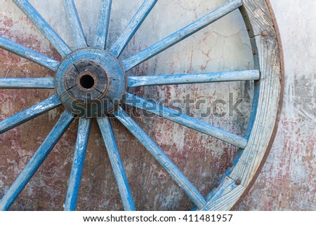 Part of old ironed blue wagon or carriage wheel on old wall with peeling paint - stock photo