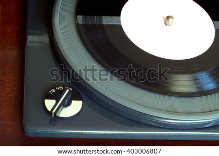 Part of old vintage three speed record player playing vinyl record with white label. Horizontal top view closeup - stock photo