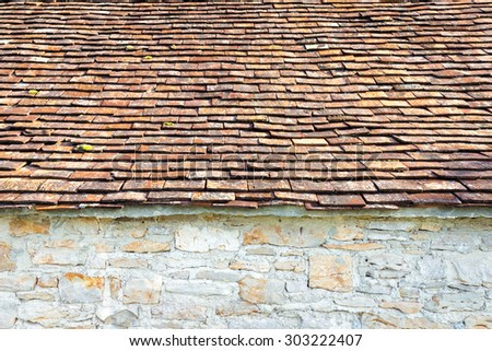 Part of red clay tiled roof and natural stone wall - stock photo