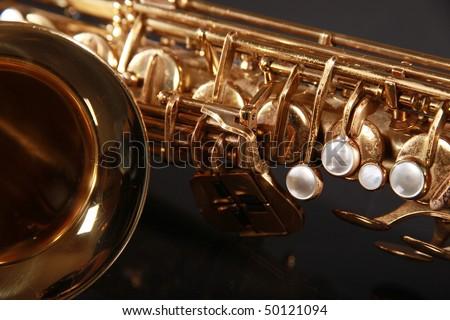 part of shiny golden saxophone on black background - stock photo