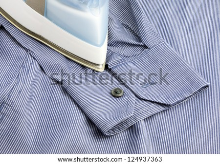 Part of steam iron on blue shirt background - stock photo