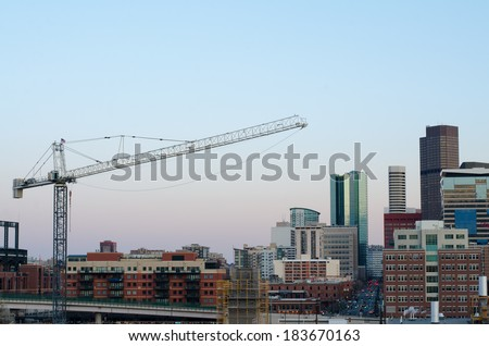 Part of the Denver skyline with a crane, taken from the 7th floor of a nearby apartment building.  - stock photo