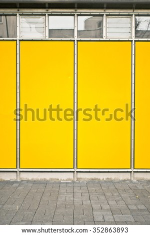 Part of the exterior of a temporary building with bright yellow panels - stock photo