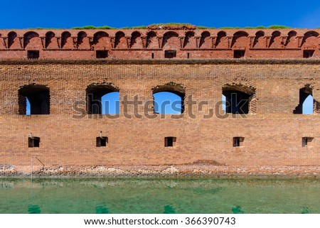 Part of the forts wall and the moat full of water at Fort Jefferson - stock photo