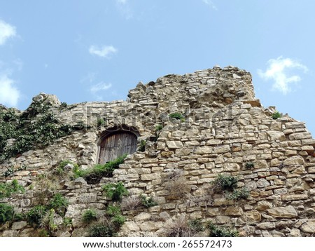 Part of the ruined medieval antique stone wall. - stock photo