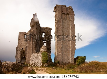 Part of the ruins of Corfe Castle, Dorset, England, with a small area of cloud covering the top of part of the ruins - stock photo