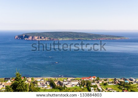 Part of the village of Perce in the Gaspesie Quebec at the bottom of the image, and in the background the sea and Bonaventure Island.(with numeric noise) - stock photo