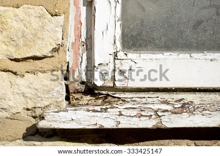 Part of the white wooden frame of an old window with peeling paint and rotten wood - stock photo