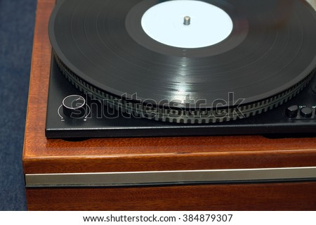 Part of vintage classic record player in wooden case with black LP vinyl record front view horizontal photo closeup - stock photo