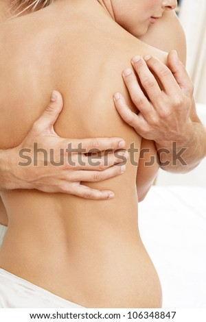 Part view of a man's hands caressing a woman's bare back. - stock photo