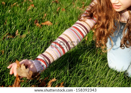 Part view of a young child girl crouching and collecting autumn dry leaves from the green grass ground in a park during a sunny and warm fall day, outdoors. - stock photo