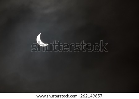 Partial solar eclipse in a grey misty sky, taken from Tehidy Country Park in Cornwall, England 20th March 2015. - stock photo