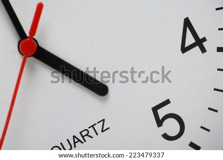 Partial view of an office clock with the hour hand pointing at five o'clock or quitting time - stock photo
