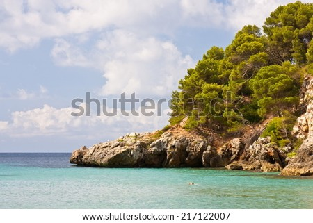 Partial view of cala Trebaluger in Menorca with much vegetation and clouds in the sky - stock photo