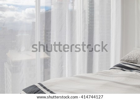 Partial view of white soft bed and transparency curtain with tall buildings and blue sky visible in the background - stock photo