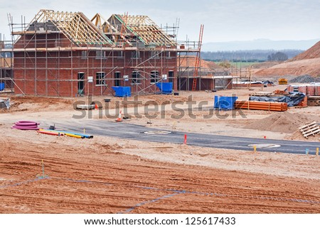 Partially built residential housing building site with homes in early stages of construction - stock photo