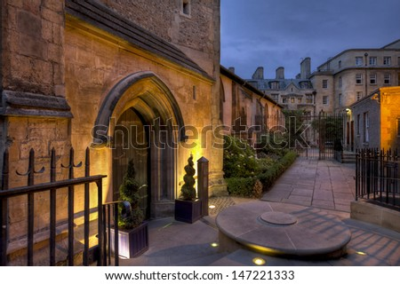 Partially illuminated night time view of St Michael Church courtyard Cambridge taken from Trinity street - stock photo
