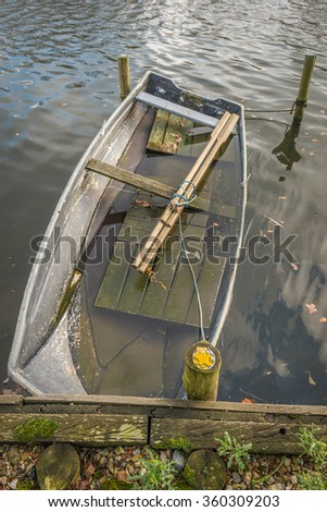 Partially sunken moored iron rowboat with wooden oars seen from above from ashore. - stock photo