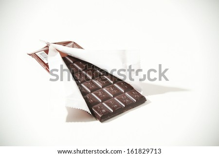 Partially unwrapped milk chocolate bar on white background - stock photo