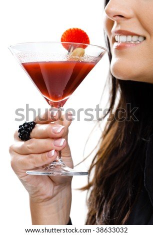 Partially visible young woman holding glass of cocktail. Selective focus on hand. - stock photo