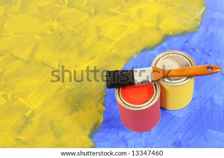 Partly finished blank blue and yellow painted floor with paint cans and paintbrush.  Space for copy. - stock photo
