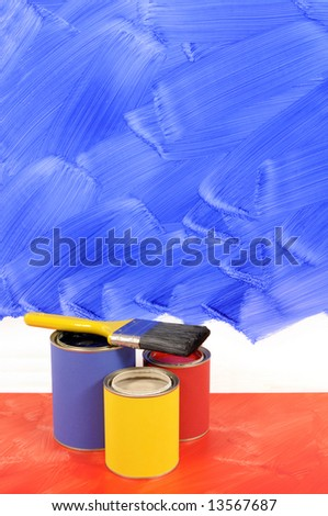 Partly finished blank blue painted wall with paint cans and paintbrush.  Space for copy. - stock photo