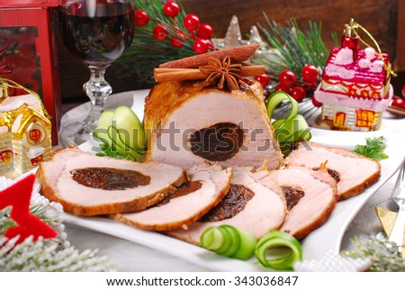 partly sliced roasted pork loin in honey glaze stuffed with plum for christmas dinner - stock photo
