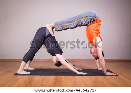 Partner yoga pose of double downward dog by a couple within a studio - stock photo