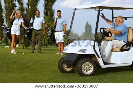 Partners meeting on golf course, greeting each other happy. - stock photo