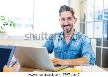 Partners working at desk using laptop and tablet in the office - stock photo