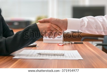 Partnership concept. Businessman and woman sitting behind desk with agreement and shaking hands on blurred background. - stock photo