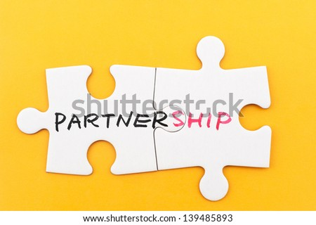 Partnership word written on two pieces of white paper jigsaw puzzles - stock photo