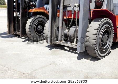 Parts of forklift loader for warehouse works outdoors. Forklift loaders tires - stock photo