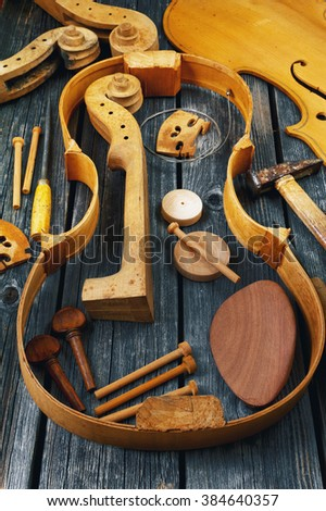 Parts of the violin on wooden background - stock photo