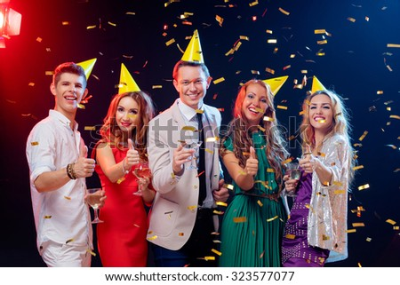 Party and celebration. Group of five happy smiling friends having fun together among confetti in night club. - stock photo