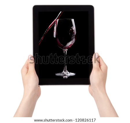 party background with Red wine splashing on a digital tablet with woman hands - stock photo