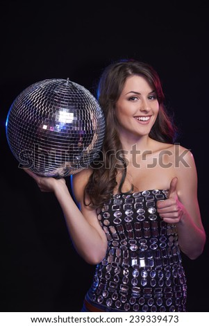 Party, celebration concept. Happy beautiful woman in evening dress holding disco ball and giving approving sign over black background - stock photo