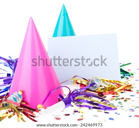 Party decorations of hats, noisemakers and confetti with a blank envelope - stock photo